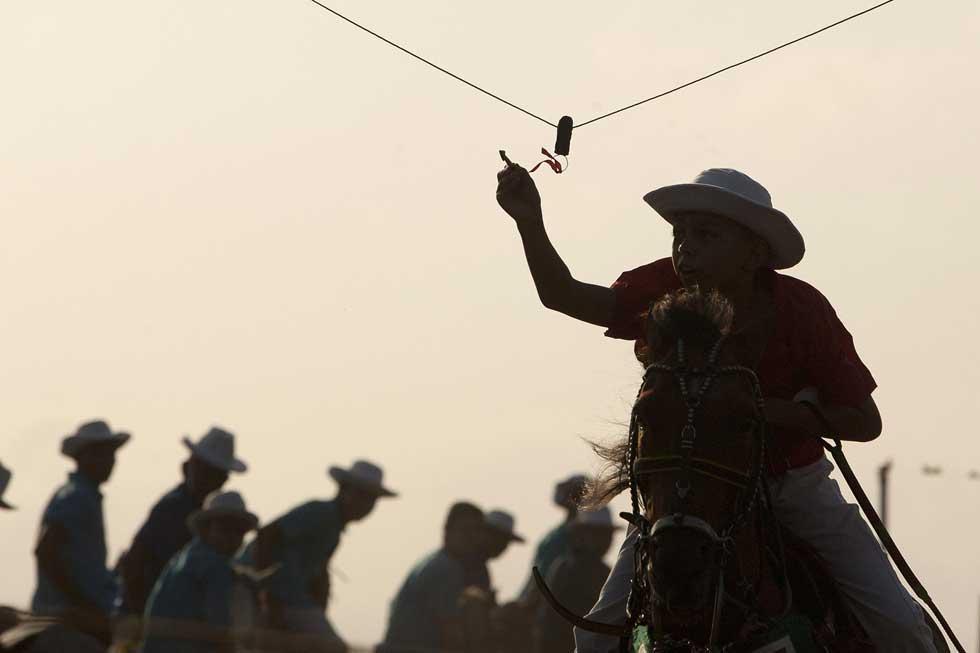 Brasil, 25.12.2011 | O jovem participante tenta cavalgar e enfiar uma linha numa agulha durante uma competição, a Marujada, em Bragança (Pará).