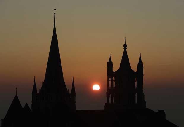 Suíça, 27.12.2011 | O sol põe-se entre os pináculos da catedral de Notre Dame em Lausana