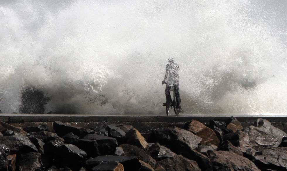 Índia, 28.12.2011 | O ciclista e a onda, num porto de Chennai. Toda a costa foi colocada em alerta devido a passagem do ciclone Thane.