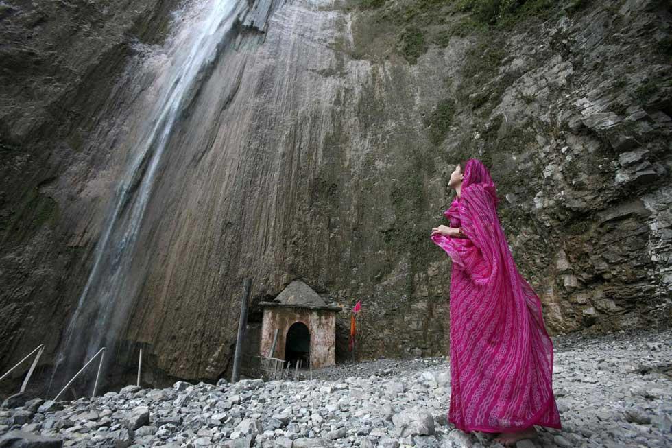 Caxemira (administrada pela Índia), 28.12.2011 | Uma mulher observa uma queda de água após ter realizado as suas orações no templo de Baba Dhansal at Reasi, perto de Jammu.