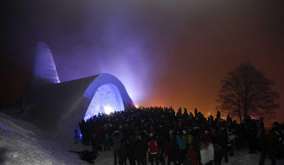 Alemanha, 28.12.2011 | A multidão aguarda o momento de entrar numa igreja católica feita de neve em Mitterfirmiansreut, Bavária
