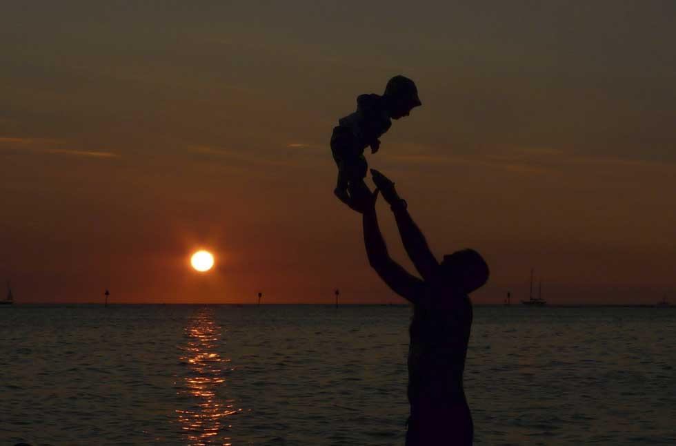 EUA, 01.01.2012 | Brincadeiras de pai e filho no primeiro pôr-do-sol do ano. Na praia de Waikiki, Honolulu, Havai