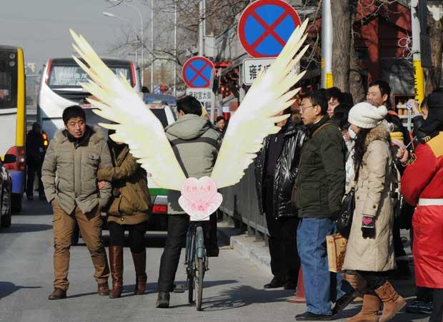 CHINA. Um ciclista com asas de anjo, perto do templo tibetano Lama em Pequim