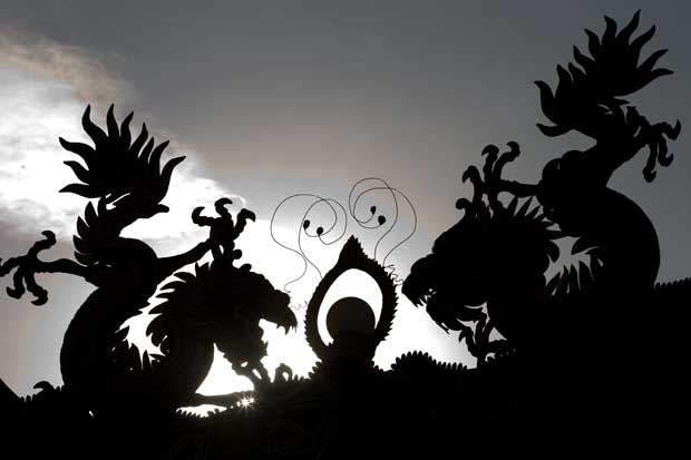 MALÁSIA. A silhueta do dragão ao nascer do sol num templo de Kuala Lumpur