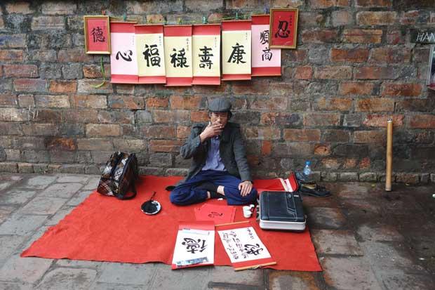 VIETNAME. Um calígrafo aguarda clientes perto do templo da Literatura em Hanoi