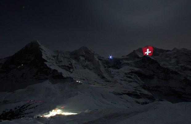 SUÍÇA. 01.01.201. Instalação gigante de luz com a bandeira suíça pelo artista Gerry Hofstetter na montanha Jungfrau. Celebra os cem anos dos caminhos de ferro na montanha. É a mais elevada estação de comboio da Europa, a 3454m de altitude