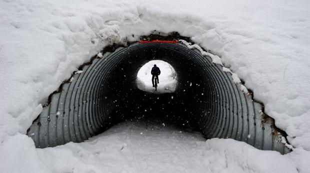 SUÍÇA. 24.01.2012. Um ciclista num túnel de Gstaad.