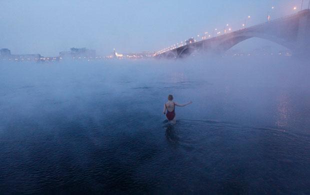 RÚSSIA. 26.01.2012. Uma participante do clube Cryophil, de nadadores de Inverno, a entrar no rio Yenisei. Estão -26ºC