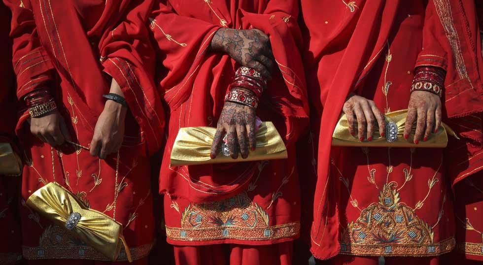 PAQUISTÃO, 29.01.2012. Três jovens paquistanesas, com as mãos decoradas com henna (fotografadas em Karachi, durante uma cerimónia de casamento colectivo de 50 pares)