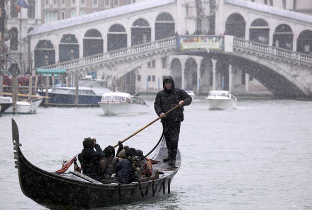 ITÁLIA. 01.02.201. Neve sobre Veneza mas isso não impede o gondoleiro de guiar os passageiros pelo Grande Canal.