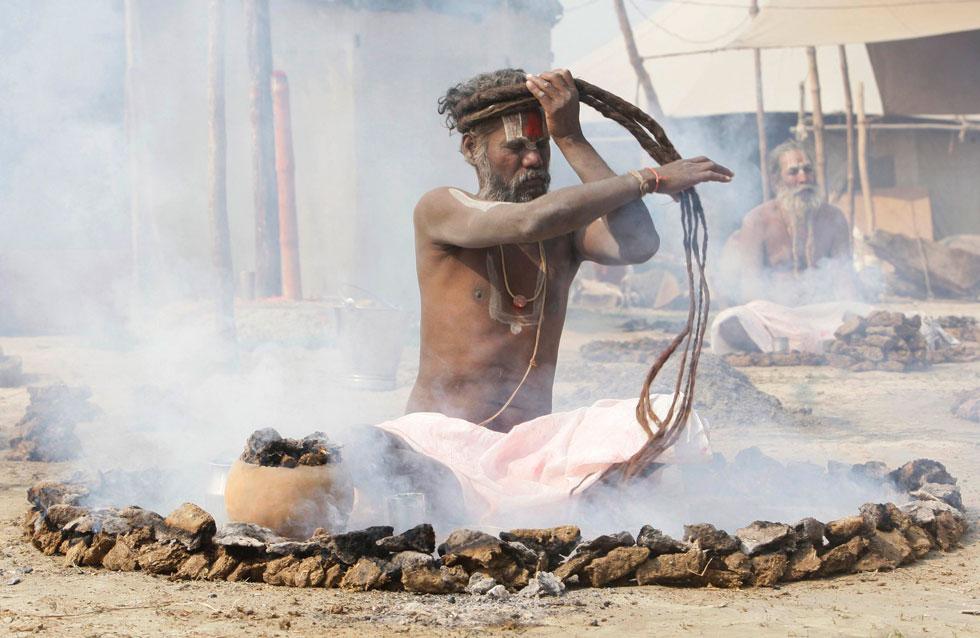ÍNDIA, 30.01.2012. Um Sadhu ata o seu cabelo sentado num círculo de fogo durante uma cerimónia de oração pela paz no mundo. Em Sangam, Allahabad.