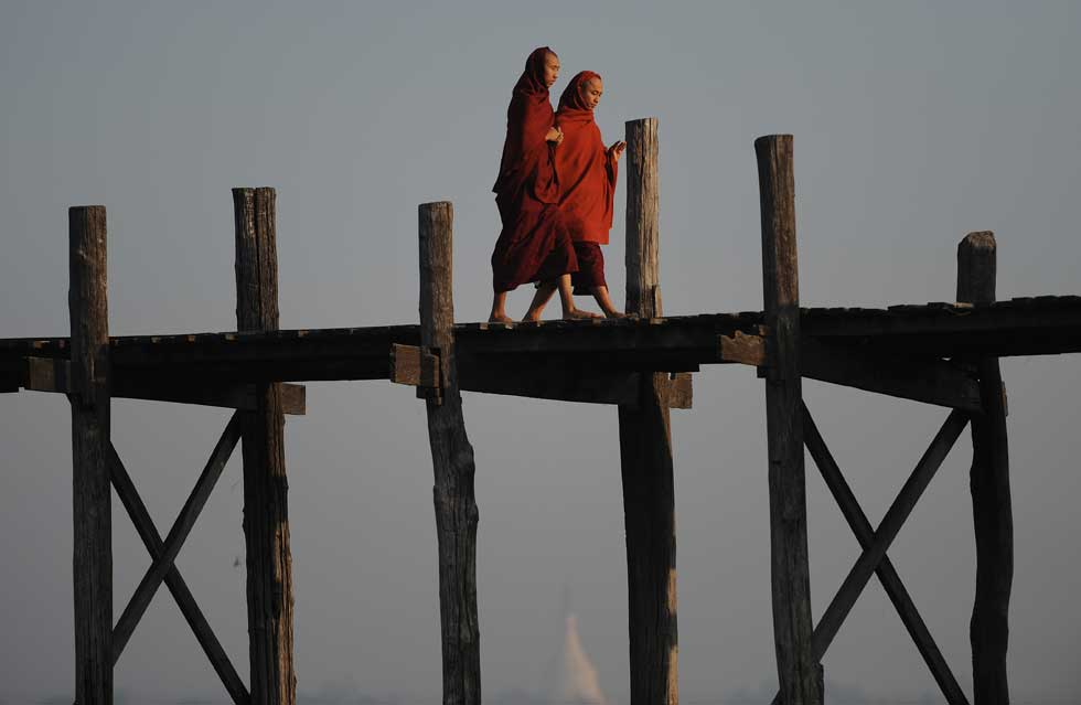 BIRMÂNIA/MYANMAR, 05.02.2012. O passeio de dois monges budistas, a cruazar o lago Taungthaman em Amarapura. É a maior ponte pedestre em madeira (teca) do mundo com 1300 metros.
