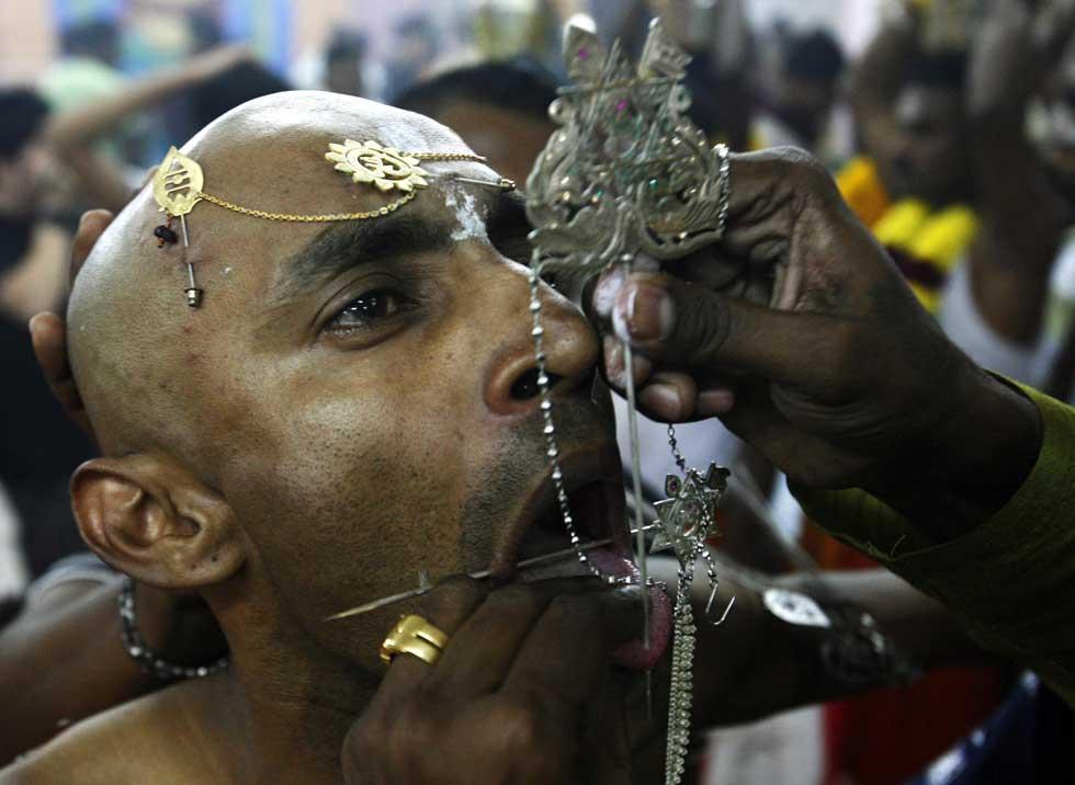 SINGAPURA, 07.02.2012. Um devoto Guna recebe um piercing na língua durante o festival Thaipusam.