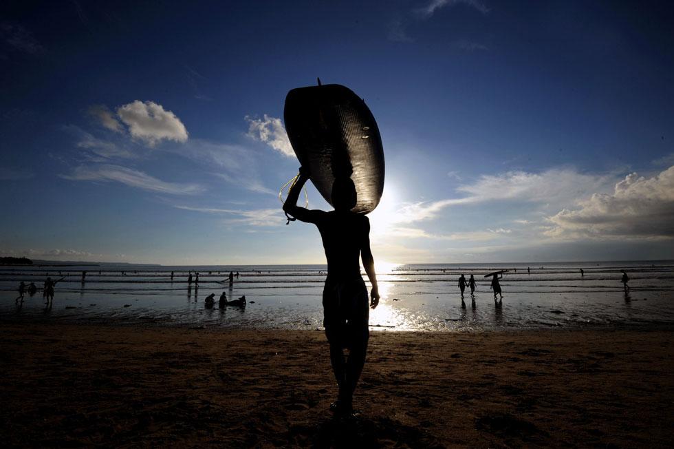 INDONÉSIA, 12.02.2012. Um surfista transporta a sua prancha na praia de Bali.