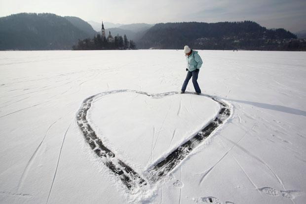 ESLOVÉNIA. Uma rapariga desenha um coração no gelo, no lago Bled, no dia de São Valentim.