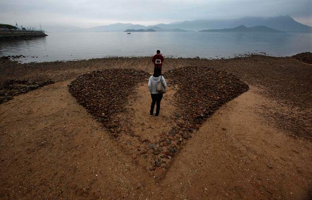 CHINA. E um coração esculpido em areia e pedra, em Hong Kong. Mede 6mx7m.  O rapaz mostra o ecã do seu tablet à namorada: lê-se