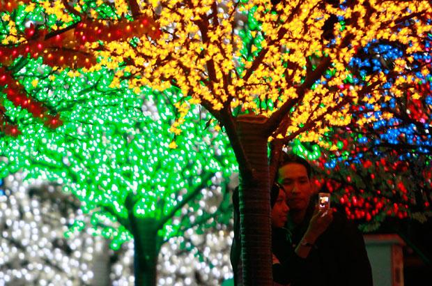 MALÁSIA. Um casal muçulmano fotografa uma decoração luminosa de São Valentim num espaço comercial. Na Malásia e noutros países islâmicos, há uma forte oposição, incluindo das autoridades no caso malaio, à celebração, considerada uma