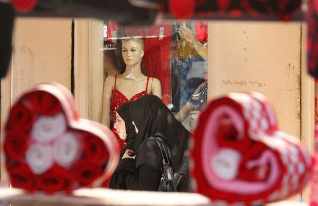 LÍBANO. Duas muçulmanas passam frente a uma boutique de lingerie, decorada para o Dia dos Namorados, em Sidon.