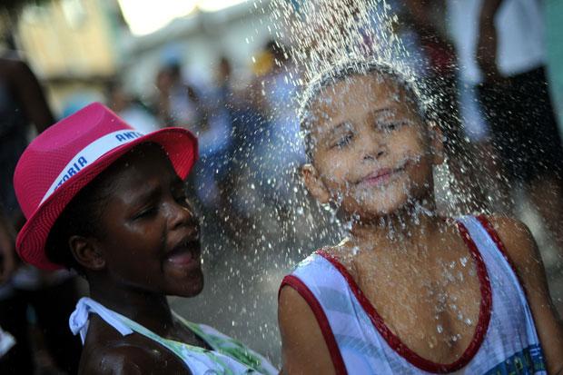 BRASIL. Um duche em plena festa, na favela do Morro do Tuiuti, organizada pela polícia e residentes.
