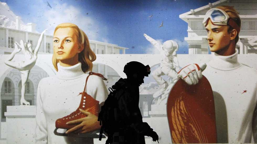RÚSSIA, 18.02.2012. Uma praticante de snowboard junto a um cartaz que anuncia a construção de uma nova estância de esqui, Gorky Gorod, em Krasnaya Polyana, a 40 km de Sochi. Nos Olímpicos de Inverno de 2014, Gorky Gorod será a vila olímpica dos media.