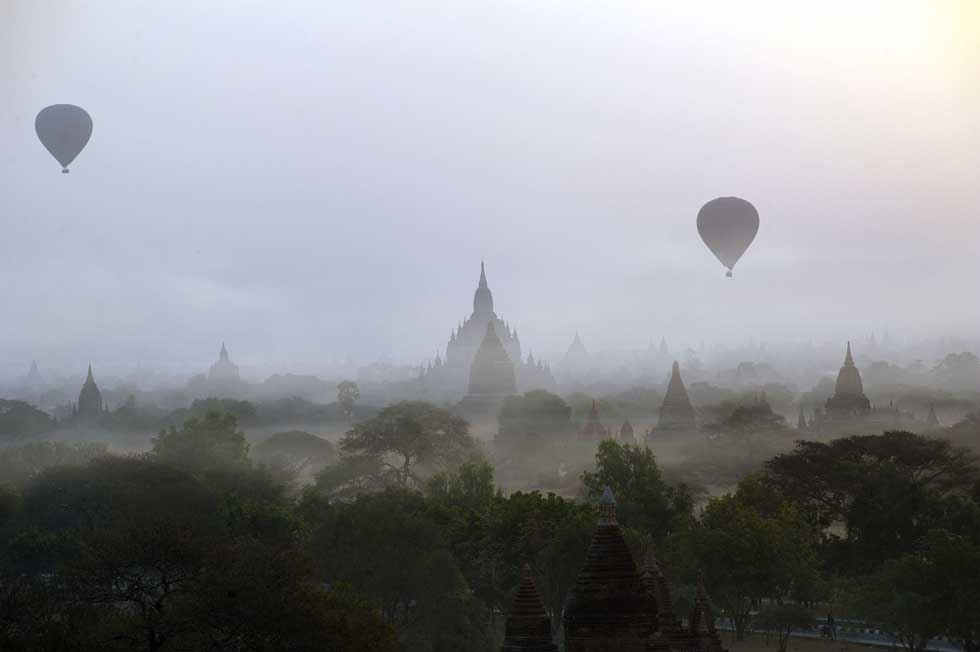 BIRMÂNIA/MYANMAR, 26.02.2012. Balões de ar quente passeiam turistas sobre os templos da velha cidade de Bagan