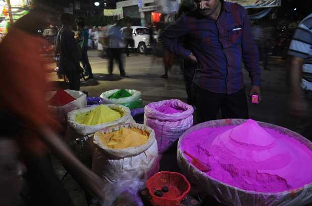 Vendedores de rua aguardam os clientes dos pós coloridos