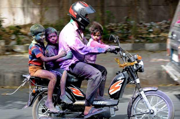 Pai e filhos em banho de cor pelas ruas de Nova Deli