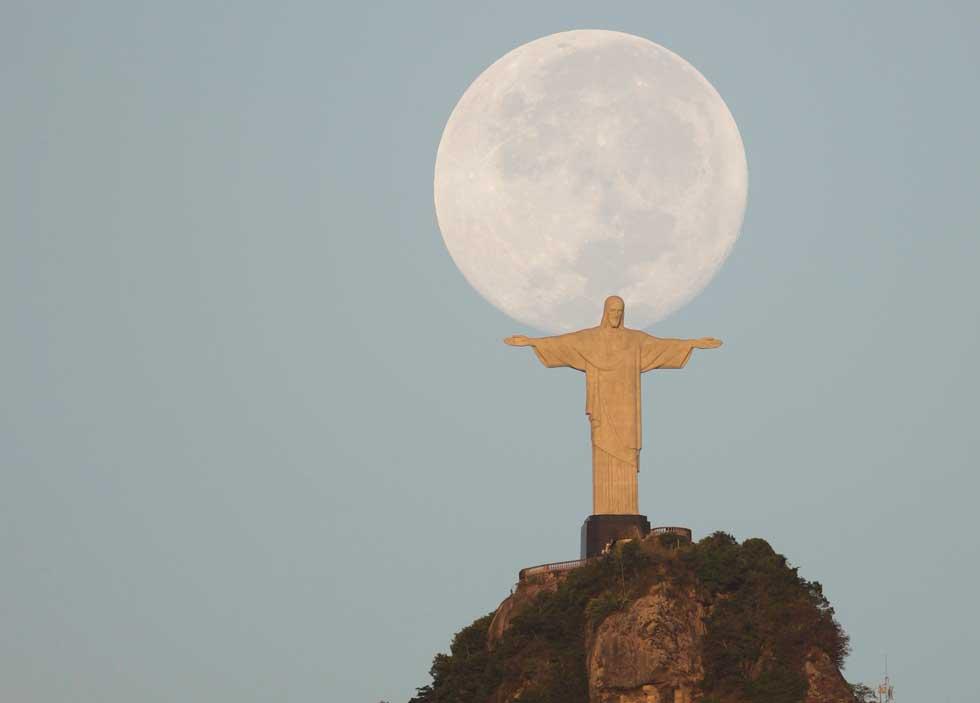 BRASIL, 09.03.2012. Lua cheia sobre o Cristo Redentor, no Rio de Janeiro