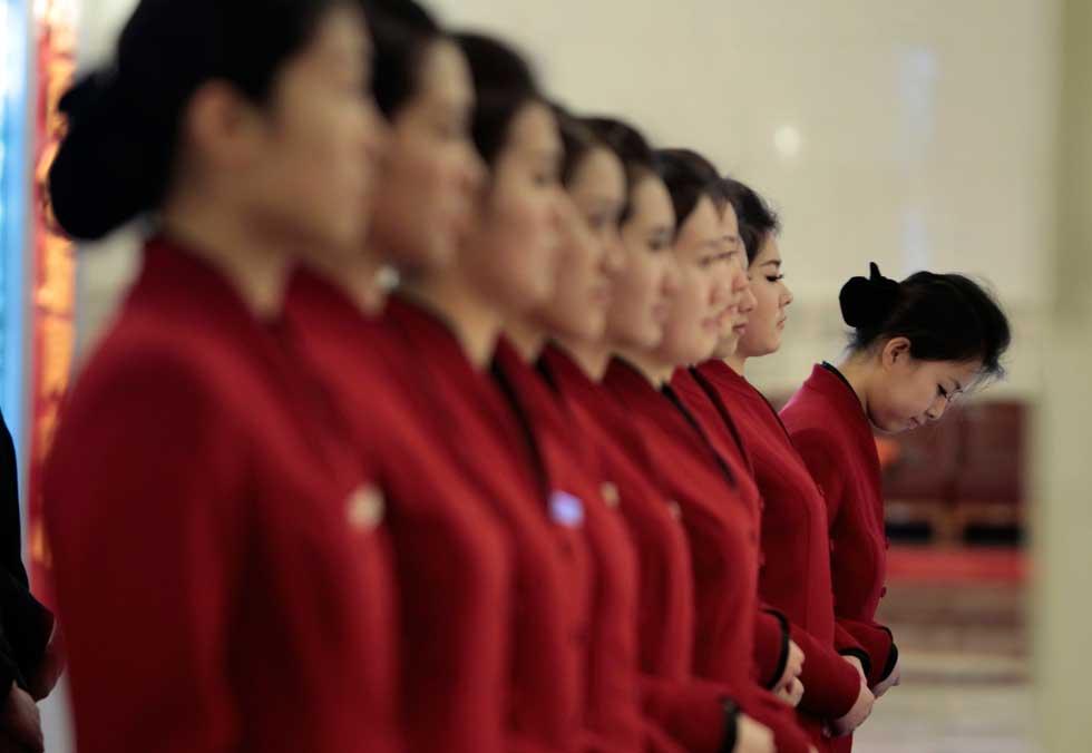 CHINA, 08.03.2012. Assistentes de chá enquanto esperam para servir os delegados da Assembleia Nacional Popular, em Pequim.