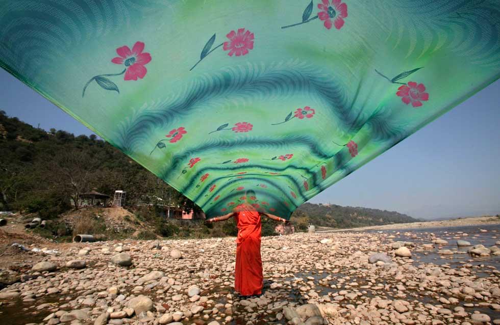 INDIA, 03.03.2012. Uma mulher seca o seu sari, após lavá-lo no rio Tawi, em Jammu