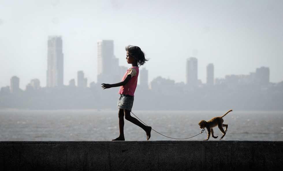 ÍNDIA, 05.03.2012. Uma miúda e o seu macaco de estimação em Mumbai