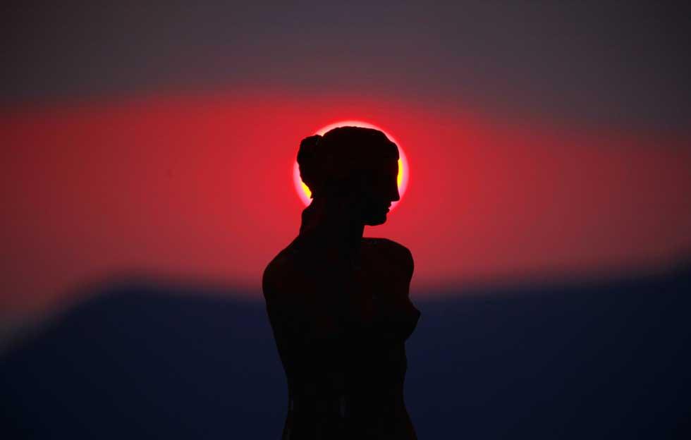 GRÉCIA, 15.03.2012. Uma réplica da estátua da deusa Afrodite de Milo sob um miraculoso pôr-do-sol visto da ilha de Santorini