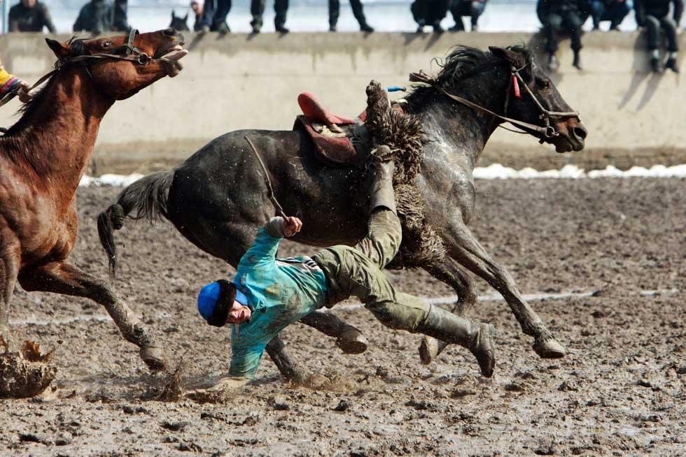 QUIRGUISTÃO, 20.03.2012. Queda de cavalo em Bishkek, capital do país, durante um festival de Kok-boru. O jogo é uma espécie de polo mas em vez de bolas usam carcaças de cabras