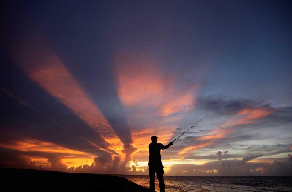 Um pescador nos arredores de Havana sob um miraculoso pôr-do-sol