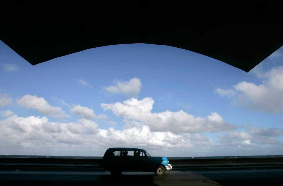 Um carro vintage passa perto de um prédio na avenida principal de Havana, El Malecón