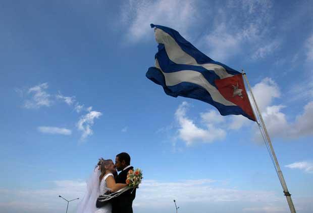 Um noivo cubano beija a sua noiva canadiana sob a bandeira de Cuba, em Havana