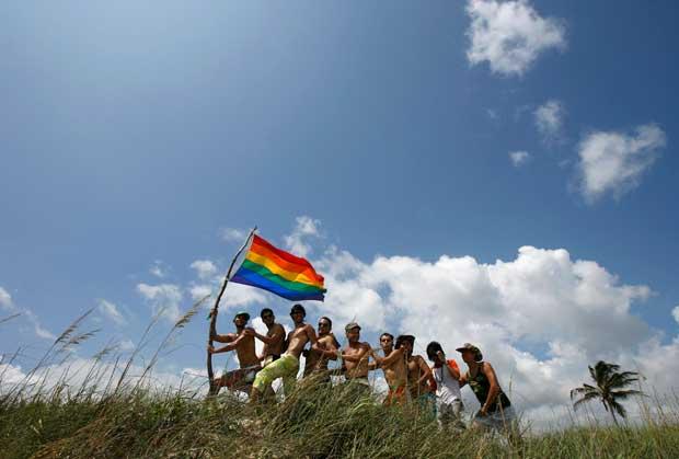 Sinais da abertura: um grupo de homens com a bandeira arco-íris da comunidade gay durante a abertura de um encontro de Verão numa praia perto de Havana