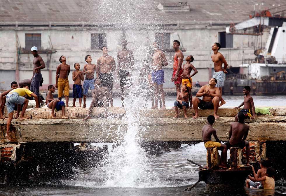 Saltos para a água no porto de Havana. Ganha quem maior repuxo causar