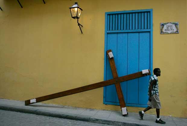 Um homem passa perto de uma cruz durante a Via Crucis, procissão da sexta-feira santa