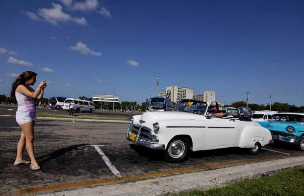 Uma turista fotografa um carro vintage americana na Praça da Revolução