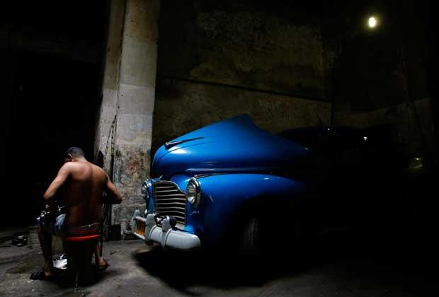 A reparar um dos velhos carros que se tornaram imagem de marca de Cuba
