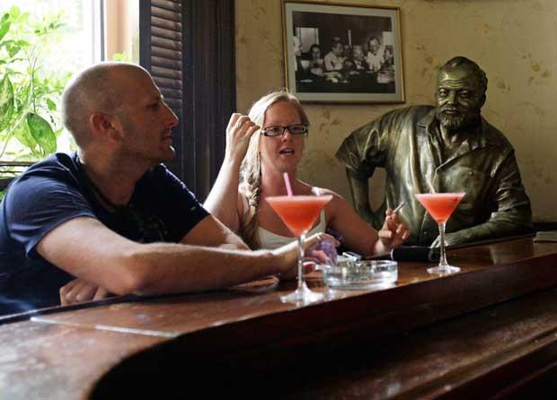 Turistas e os seus daiquiris com um Hemingway de bronze em tamanho real no lugar que costumava ocupar no bar Floridita, em Havana