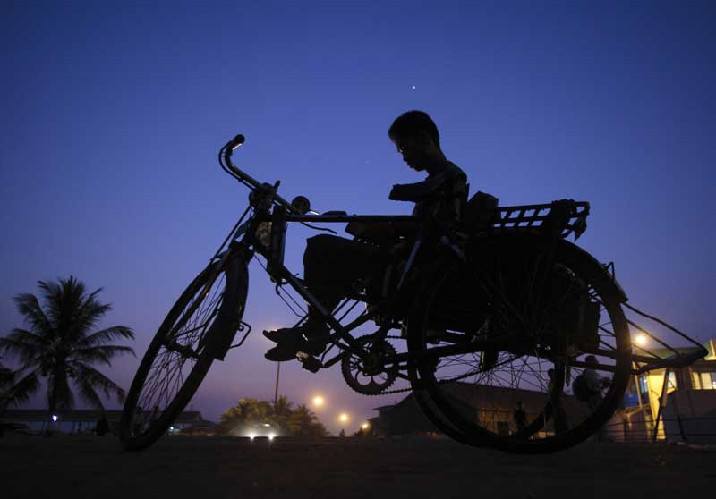 BIRMÂNIA/MYANMAR, 24.02.2012. O condutor de um triciclo-táxi aguarda clientes junto ao rio Yangon.