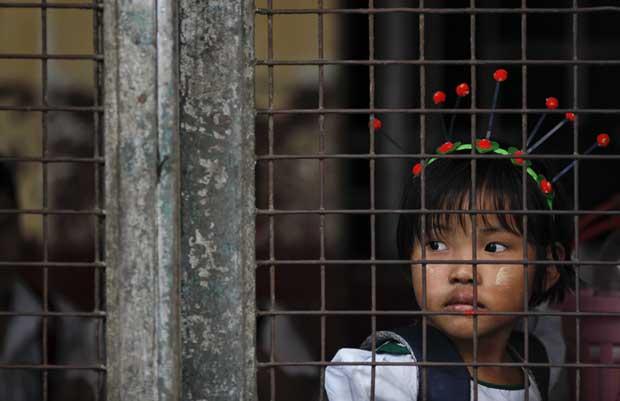 Um olhar de evasão. A pequena estudante espera na escola que os pais a venham buscar.