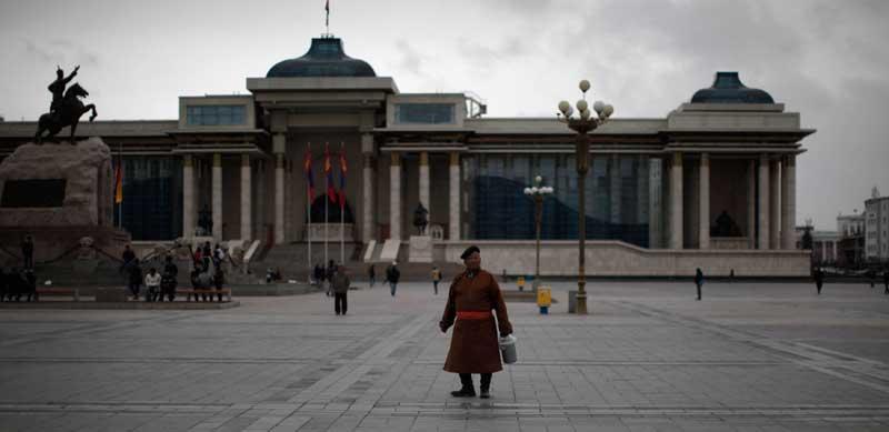 Um residente da capital em traje tradicional na praça central da cidade