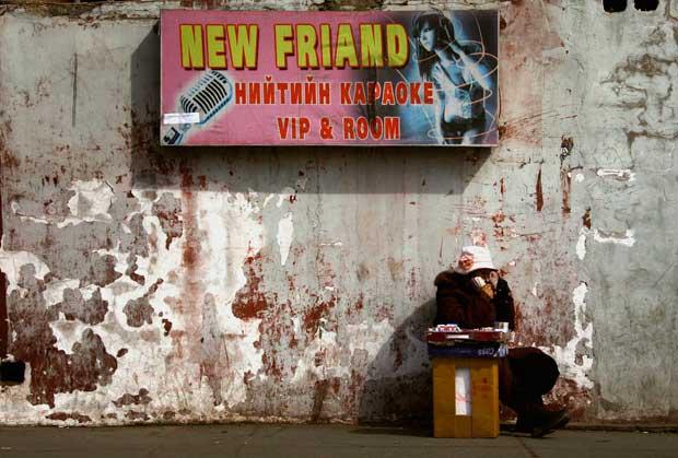 A vender cigarros nas ruas da capital - o poster anuncia um bar