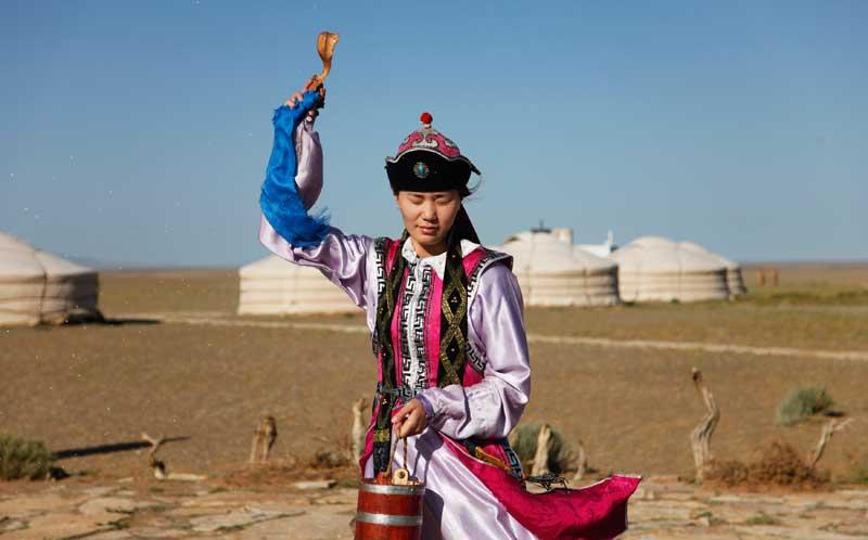 Preservar as tradições também para mostrar ao turista: Uma rapariga realliza uma velha cerimónia de despedida, atirando arroz aos turistas, num campo em Bayanzag, Omnogovi