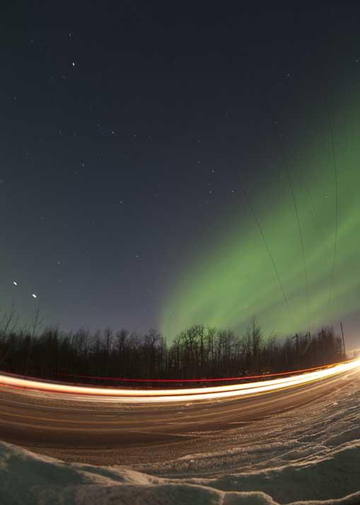Aurora Boreal sobre uma estrada iluminada pela velocidade do trânsito perto de Butte, Alasca, EUA  (09.03.2012)