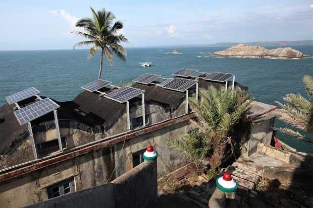 Vergula, a norte de Goa, Índia. O barco no horizonte e em primeiro plano casas com painéis solares. Novembro 2011