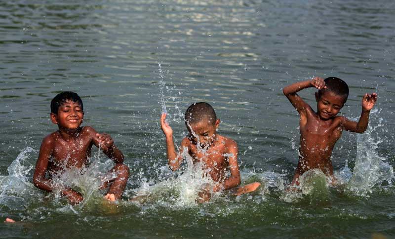 BANGLADESH, 08.05.2012 | Crianças a brincar num lago durante uma tarde quente em Dhaka.